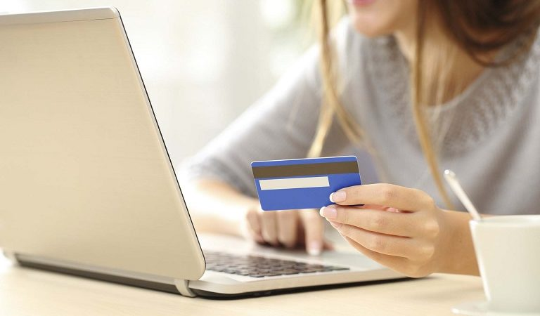 Close up of a happy woman hand buying online with a laptop and paying with a credit card